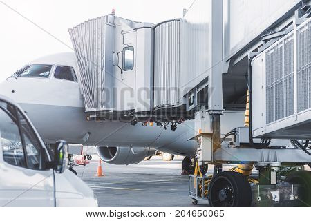 Cabin of big vehicle joining to white big plane at airdrome . Copy space