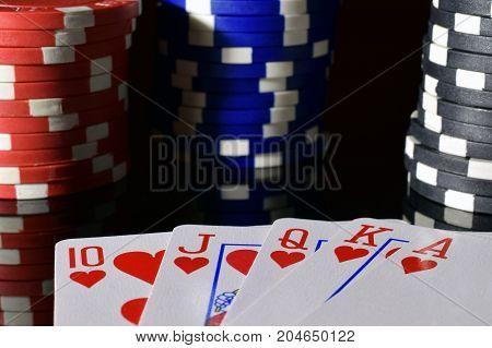 Poker hand royal flush on black reflective board. Poker chips on background.