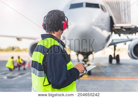 Technical staff wearing headset while checking plane. He typing notes in electronic tablet. He turning back to camera