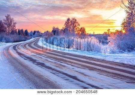 winter landscape with sunsetroad and forest. path winter covered with snow in rays of sunset. wintry snowy road in ice