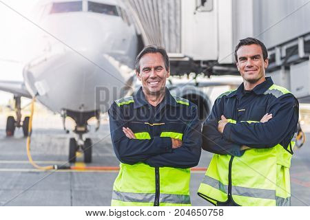 Portrait of cheerful mechanics standing near each other at airport outdoor. They looking at camera
