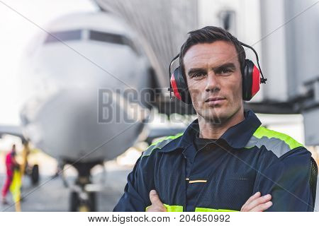 Portrait of serious male engineer working at airport. He looking at camera