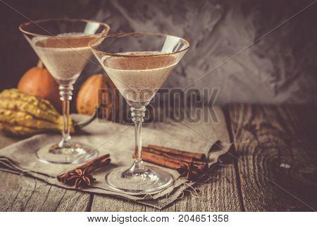 Autumn martini cinnamon cocktail, rustic background, copy space