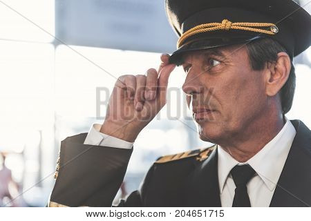 Side view serene aviator keeping hat by hand while situating at airport. Copy space. Job concept