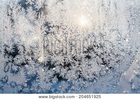 wintry frosty pattern on glass. abstract background of ice frozen window. winter day sun shine through frosted glass on window.