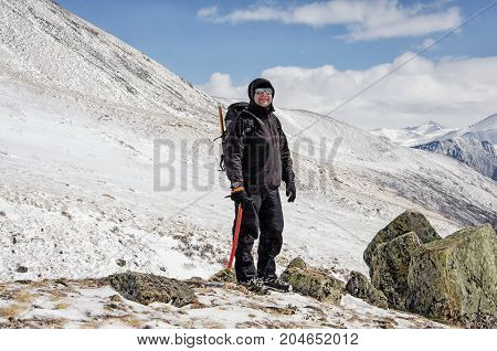 Hiker stays and with hands up on a snow mountain hill and enjoy beautiful view. Russia.