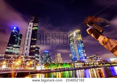 A view across the Yarra river at the landmark of Melbourne downtown during the city's nightime.