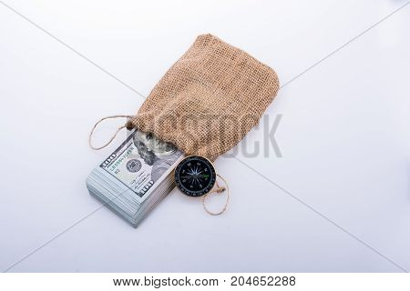 Compass and bundle of US dollarin a sack on a white background
