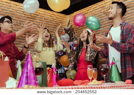 Young men and women group throwing balloon in christmas party together with dancing drinking wine happy and fun in new year celebrate