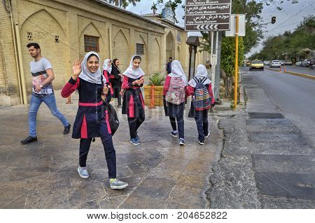 Fars Province Shiraz Iran - 18 april 2017: An Iranian schoolgirl in school uniform is smiling and waving a hand at a photographer on a city street.