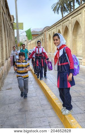 Fars Province Shiraz Iran - 18 april 2017: Iranian children return from school on a city street.