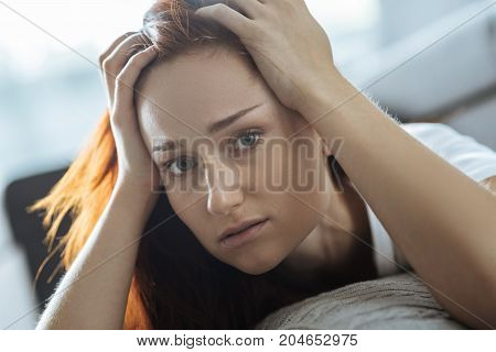 This is migraine. Cheerless pretty young woman holding her head and looking at you while having migraine