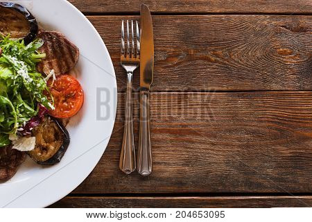 Medallions with grilled vegetables on white plate. Meat, tomatoes, eggplant and green salad with grated cheese, serving in restaurant, top view with free space on wooden background on right