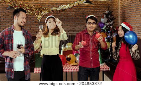 Young men and women group christmas party together with dancing drinking wine happy and fun in new year celebration