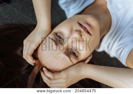 Painful look. Unhappy gloomy cheerless woman holding her head and looking at you while suffering from migraine