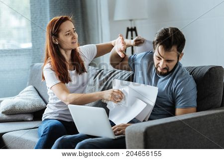 Emotional stress. Angry furious unhappy woman holding sheets of paper and attacking her boyfriend while having a quarrel with him