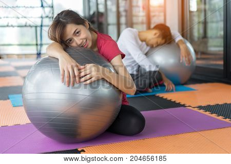 Young asian woman and man fitness exercise aerobics with yoga ball indoor for building muscle slim body and strong perfect Sleeping tired
