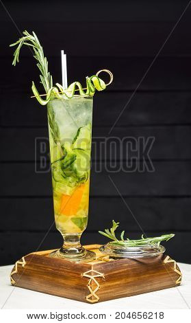 Wineglass with cocktail of cucumber and rosemary on wooden tray.