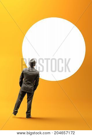 A smart businessman staring into a blank white circle.