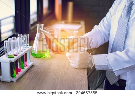 Scientist man with glasses working tablet reserch and conducts experiments by synthesising compounds in laboratory and the test tube