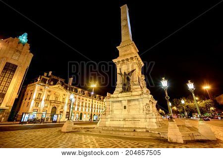 A popular Obelisk in Praca dos Restauradores or Restoration Square in honor of Portuguese Independence from Spain in Lisbon downtown, Portugal. Spectacular urban night landscape.