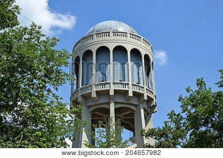 Old water Tower in the city and trees