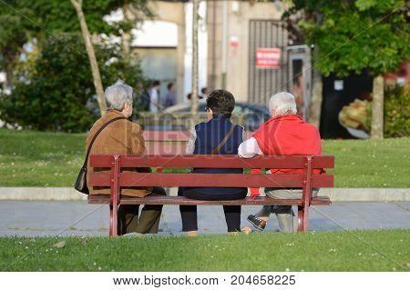 three elderly women on a street bench