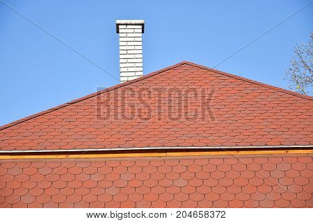 House roof and smoke stack against sky