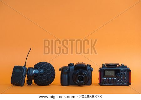 equipment for field video production camera microphone recorder on orange background