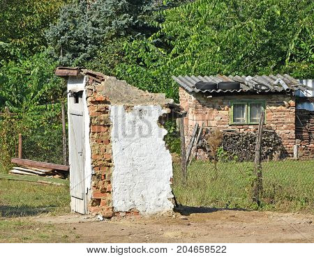 Ruined toilet building outdoors in the village next to a woods