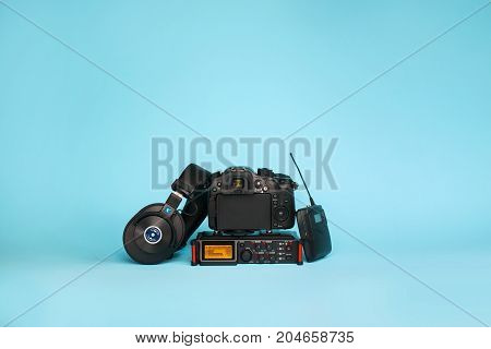 equipment for field video production camera boom mic recorder and wireless system on blue background
