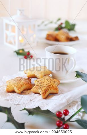 Homemade Christmas cookies cup of coffee holly and white lantern