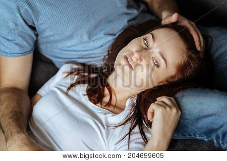 Too much stress. Sad cheerless red haired woman lying on her boyfriends legs and thinking about her problems while being stressed out