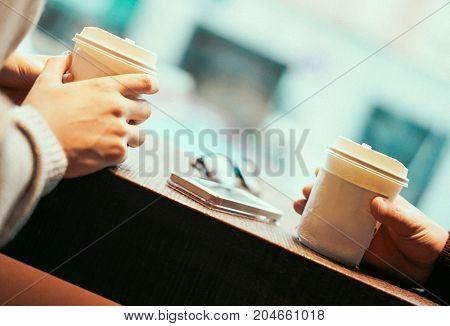 Two friends drinking coffee in paper take away cup - People having a break sitting in bar restaurant toasting cappuccino - Tilted composition - Soft focus on right person finger - Retro filter