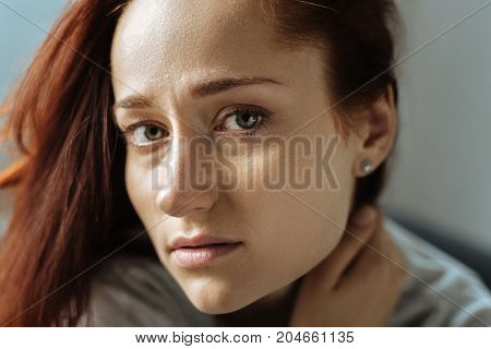 Beauty in sadness. Portrait of an unhappy beautiful young woman looking at you while suffering from depression