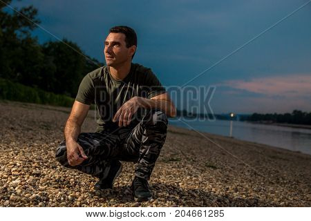 Handsome man in military style seating on rocky beach dramatic look