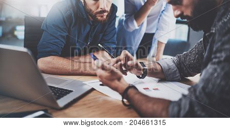 Teamwork concept.Group of three coworkers working together in modern coworking studio.Bearded man using smartphone showing new startup project.Horizontal cropp.Blurred background