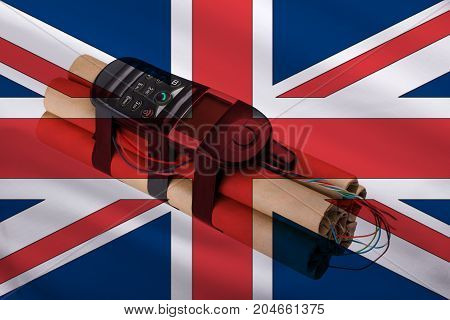 Explosion in a bomb with a phone on the background of the British flag. Attack of the terrorist act in London