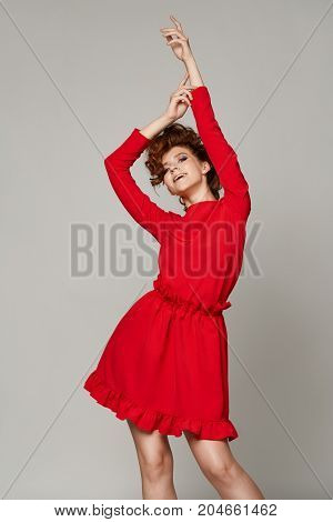 Portrait of beautyful woman in red dress on gray background at studio emotion  happyness