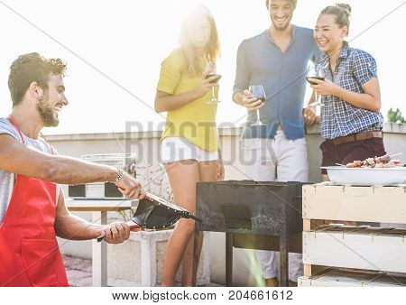 Group of friends having fun at rooftop barbecue party - Happy chef making fire with bellows for bbq dinner - Focus on left man - Youth food friendship concept - Original color sun tones editing