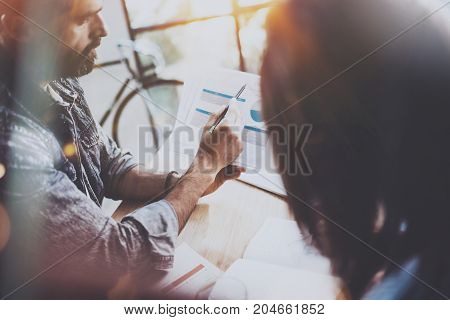 Young coworkers working together in modern office.Bearded man talking with colleague and showing paper documents.Business people brainstorming concept.Horizontal.Blurred background.Flares.