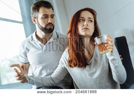 Do not touch me. Unhappy sad young woman holding a glass of whisky and not allowing her boyfriend to take it away while being alcohol addicted
