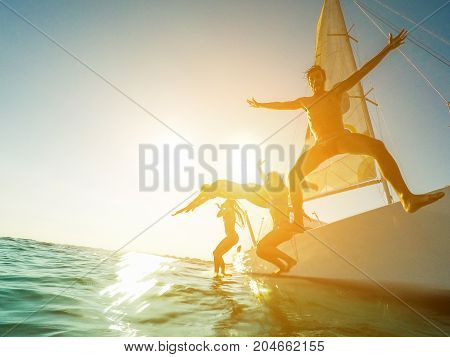 Crazy friends jumping off the boat into the ocean - Young happy people having fun diving into the sea - Travel tropical summer and concept - Soft focus on left man face - Tilted horizon composition