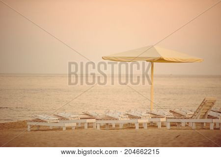 White Chaise Lounges And Umbrellas At The Sea During Sunset, Romantic Time