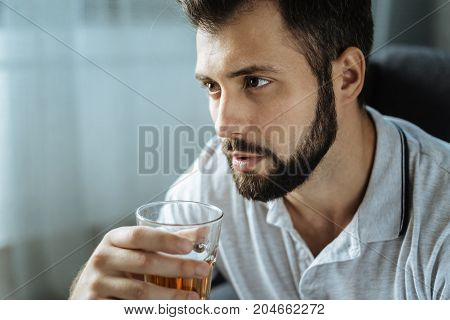 Alcoholic drink. Depressed good looking brunette man drinking whisky and thinking about his life while feeling unhappy