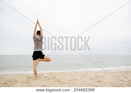 Man Practicing Yoga On The Beach In The Early Morning.