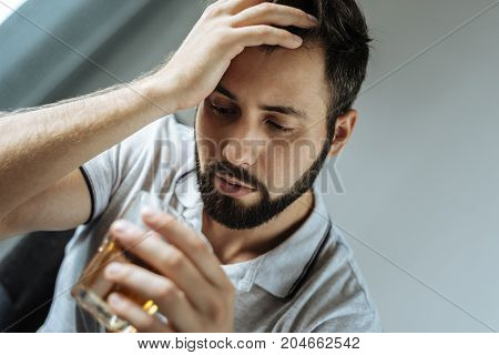 I am an alcoholic. Sad unhappy depressed man holding a glass with whisky and looking at it while trying to cope with his grief