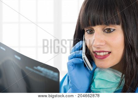 a young female doctor looking at patients x-ray and phone