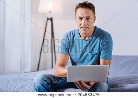 Remote worker. Handsome middle-aged man sitting in the bedroom on the bed and working on the laptop while looking at the camera