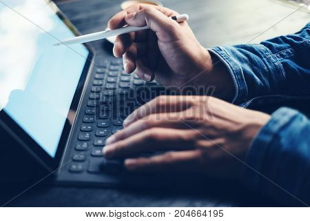 Man working at office.Closeup view of male hands typing on electronic tablet keyboard-dock station. Horizontal